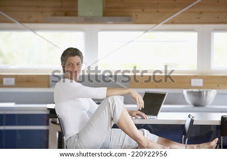 Mixed Race woman sitting next to laptop - stock photo