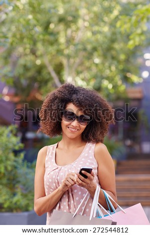 Mixed race woman wearing sunglasses and carrying shopping bags standing outdoors while sending a message on her mobile phone - stock photo