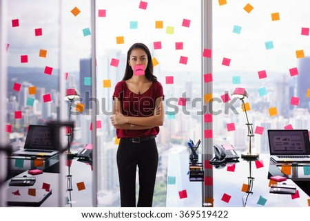 Mixed race woman working in modern office with reminders on skyscraper window. The girl feels stressed, holds a sticking note with sad emoticon on mouth. - stock photo