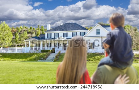 Mixed Race Young Family Looking At Beautiful New Home. - stock photo