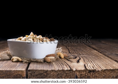 Mixed roasted and salted nuts (selective focus) on an old wooden table - stock photo