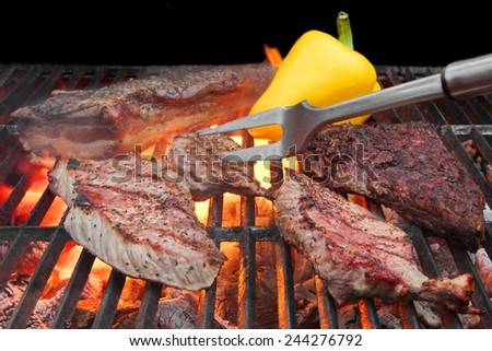 Mixed Roasted Meat on the BBQ Grill and Fork. Pork Brisket, Ribs, Beefsteaks. Flames in the Background. - stock photo