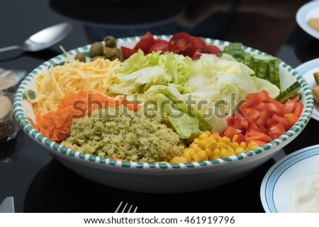 Mixed salad bowl on black glass tabletop, healthy dinner time