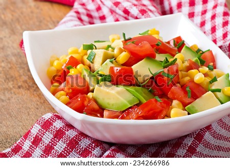 Mixed salad with avocado, tomatoes and sweet corn - stock photo