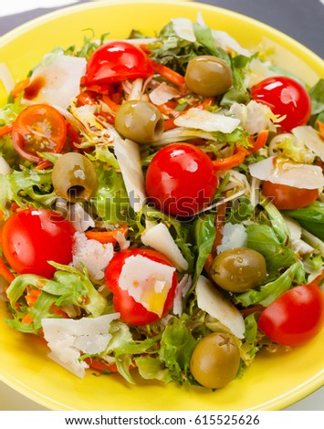 Mixed salad with olives, cheese and tomatoes on black slate.