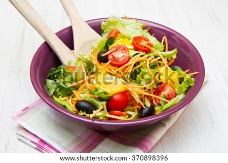 mixed salad with tomatoes in purple bowl on wood table - stock photo