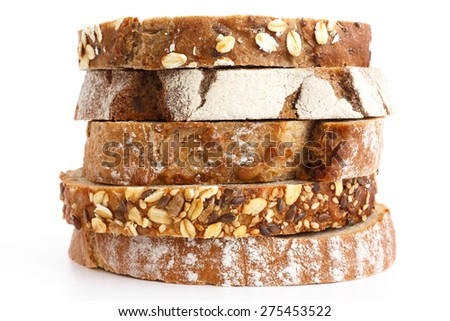 Mixed slices of health breads stacked. White surface. - stock photo