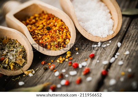 mixed spices for fish and chicken cooking and salt in wooden scoops, bay leaves and pepper corns on old vintage table