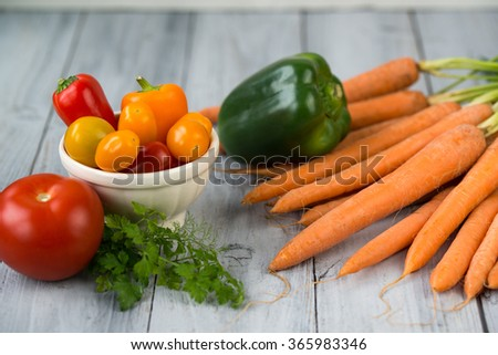 Mixed vegetables. Carrots, paprika, cherry tomatoes in a bowl, tomato and herbs on a kitchen wooden table - stock photo