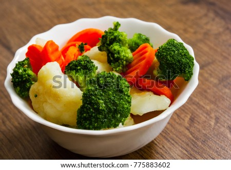 Mixed vegetables. cauliflower, broccoli and carrots in plate on a wooden background.