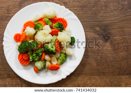 Mixed vegetables. cauliflower, broccoli and carrots in plate on a wooden background. with copy space. top view