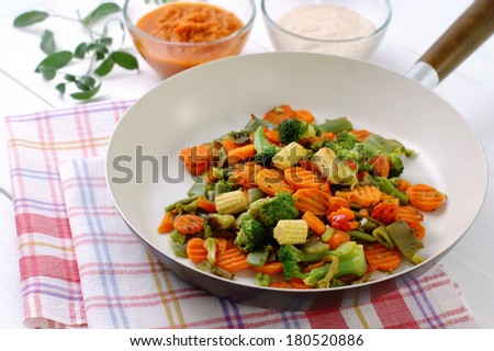 Mixed vegetables fried in a ceramic pan angle view. - stock photo