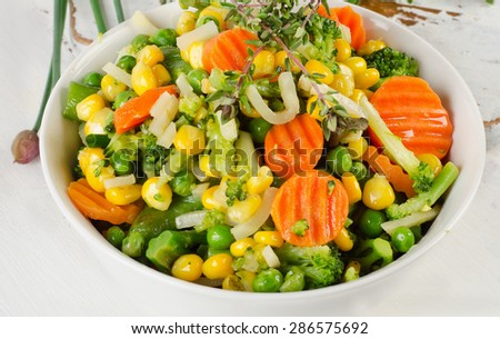 Mixed vegetables with fresh herbs in  white bowl. Top view - stock photo