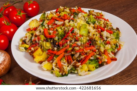 Mixed vegetables with rice in a plate on wooden table - stock photo