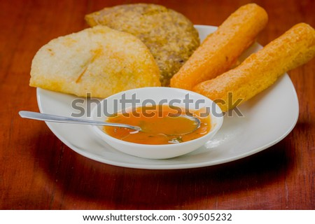 Mixed white plate of typical latin food including empanadas and a salsa bowl. - stock photo