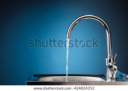 mixer tap with flowing water, blue background - stock photo