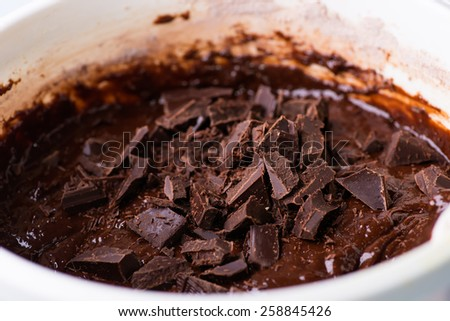 Mixing chocolate chunks in chocolate batter, selective focus, close up. The process of making chocolate batter. - stock photo