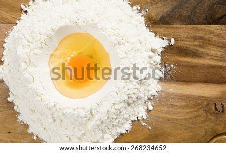 Mixing egg and flour on wooden board