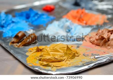 Mixing paint on aluminum foil. - stock photo