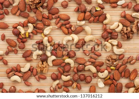 Mixture of nuts lying on a bamboo mat - stock photo