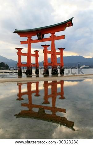 miyajima,hiroshima,japan, this is the torii gate of the famous itskushima shrine with full reflection - stock photo