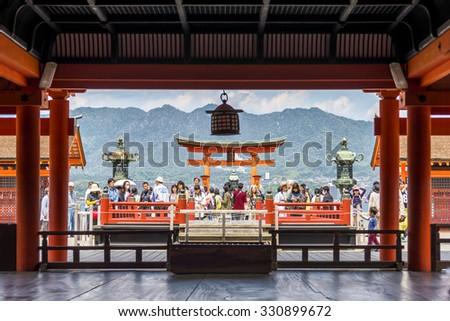 "Miyajima, Japan - April 27, 2014: View of pilgrims visiting Itsukushima Shrine. This is a shinto shrine located on the island of Itsukushima (or Miyajima), best known for its ""floating"" torii gate. - stock photo"