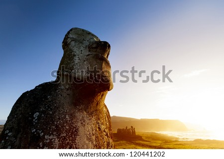 Moai looking at sea with bright blue sky and orange sea in background - stock photo