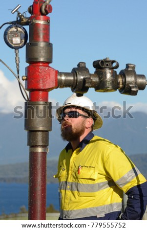 MOANA, NEW ZEALAND, OCTOBER 27, 2017: An unidentified engineer checks the guage during a pressure test on an abandoned oil well in preparation for capping the well.