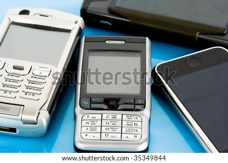 mobile and computer on blue background - stock photo