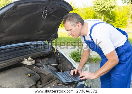 Mobile car service engineer checking car with his laptop on the road - stock photo