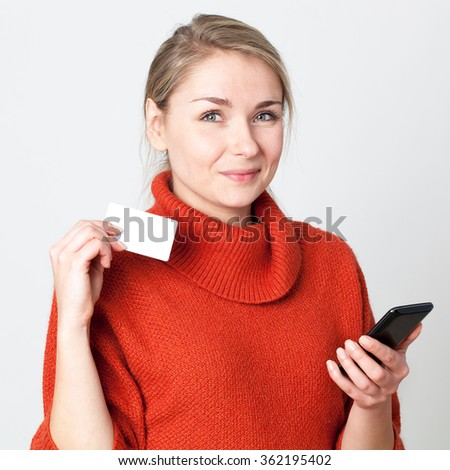 mobile commerce - happy young blond woman consuming on cell phone with copy space credit card for modern convenience, white background
