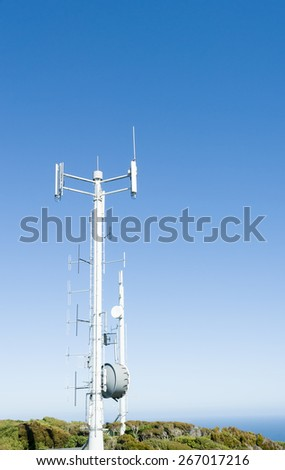 Mobile Communications tower on Bluff Hill, South Island, New Zealand stands against clear blue sky. - stock photo