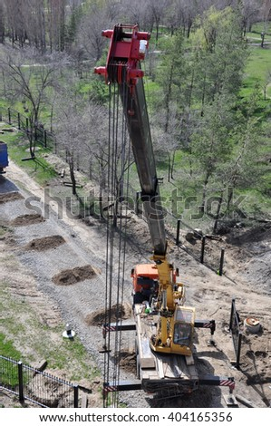 Mobile crane in work at a construction site with trees and green grass. Closeup of the upper sheave as viewed from higher position.