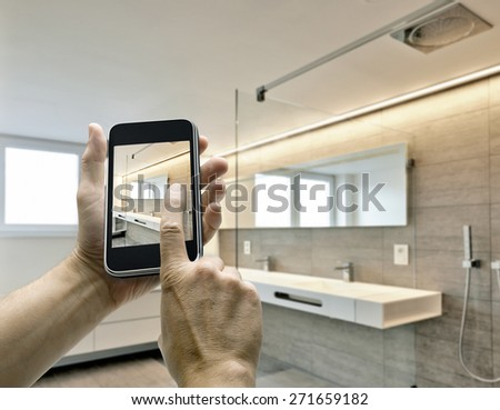 Mobile device with man hands taking picture in luxury Bathroom - stock photo