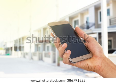 Mobile hold in hand with blur townhouse. - stock photo