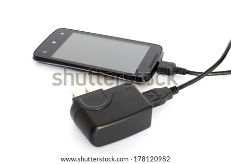 Mobile phone and charger - stock photo