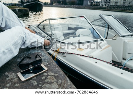 mobile phone and sunglasses on the piar near woman legs boat on background