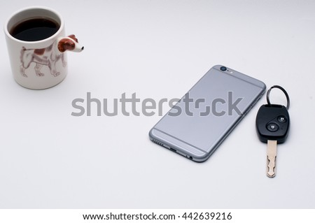 mobile phone, car key, cup of coffee, Jack Russel dog side of coffee cup, on white table - stock photo