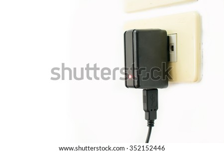 Mobile phone charger on electric outlet - stock photo