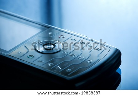 Mobile phone close-up shot. Toned in blue - stock photo