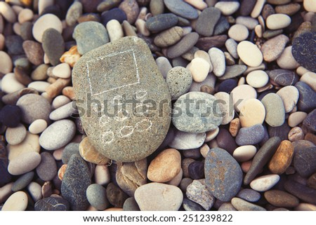 Mobile phone from stones on beach close-up - stock photo