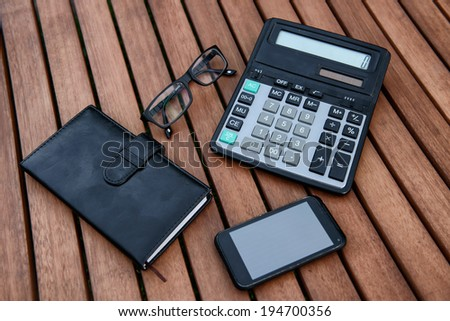 Mobile phone, glasses, calculator, notepad on wooden table. Business accessorizes concept. - stock photo