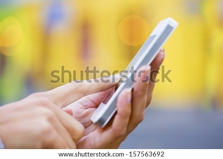 Mobile phone in a woman's hand, yellow store background, message, sms, e-mail  - stock photo