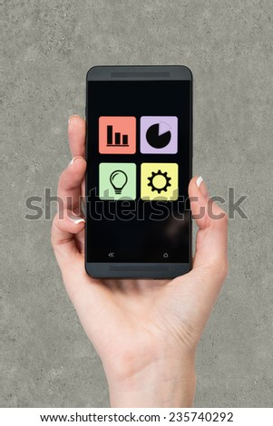 mobile phone in hand on gray background - stock photo