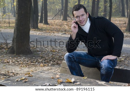 mobile phone in the park and man with smile - stock photo