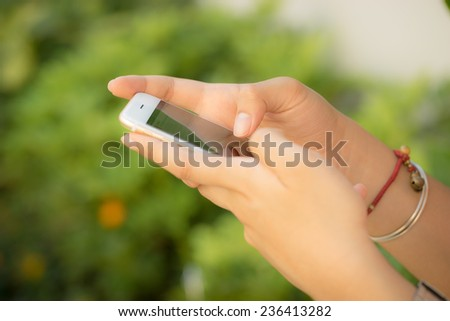 Mobile phone in woman hands - stock photo