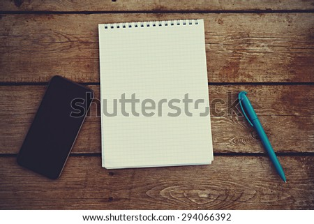 mobile phone, notebook and pen on the old wooden table - stock photo
