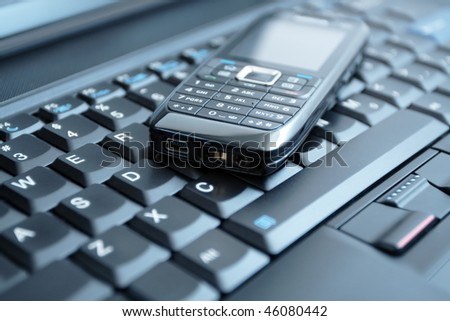 Mobile phone on laptop keyboard - business concept - stock photo
