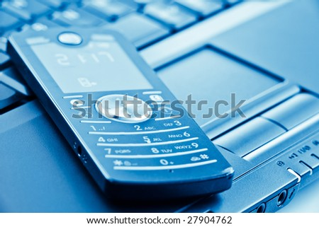 mobile phone on laptop keyboard with shallow depth of field