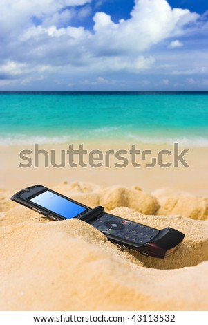 Mobile phone on sand beach - communication concept